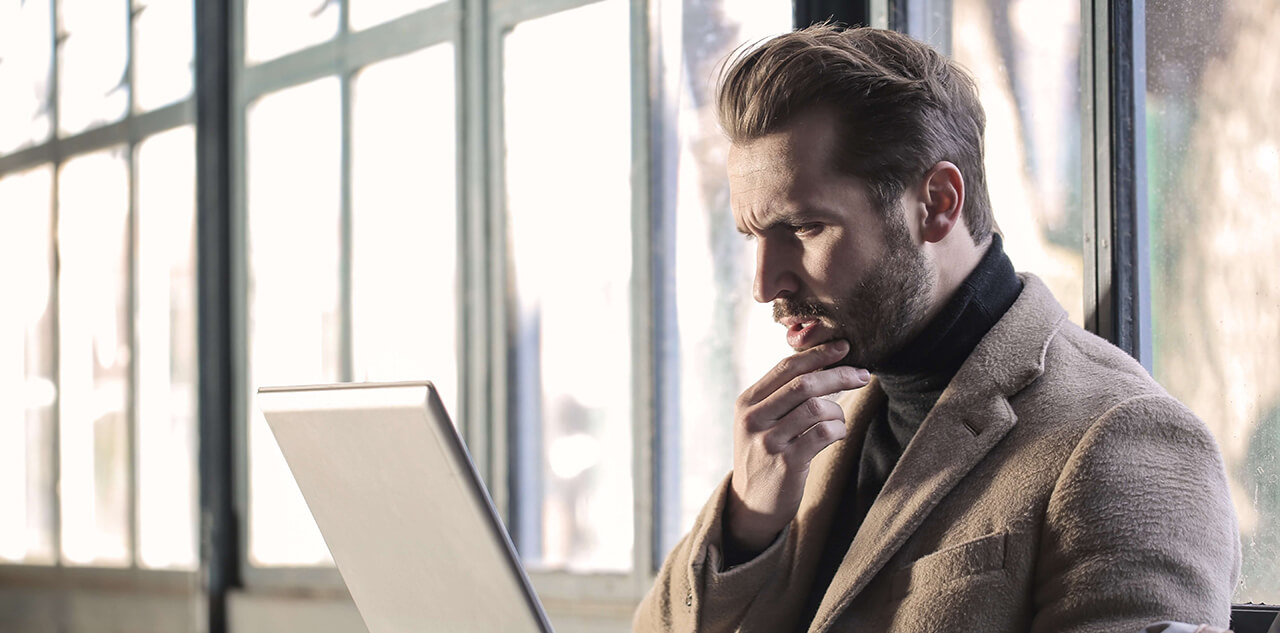 Man with serious look looking at laptop