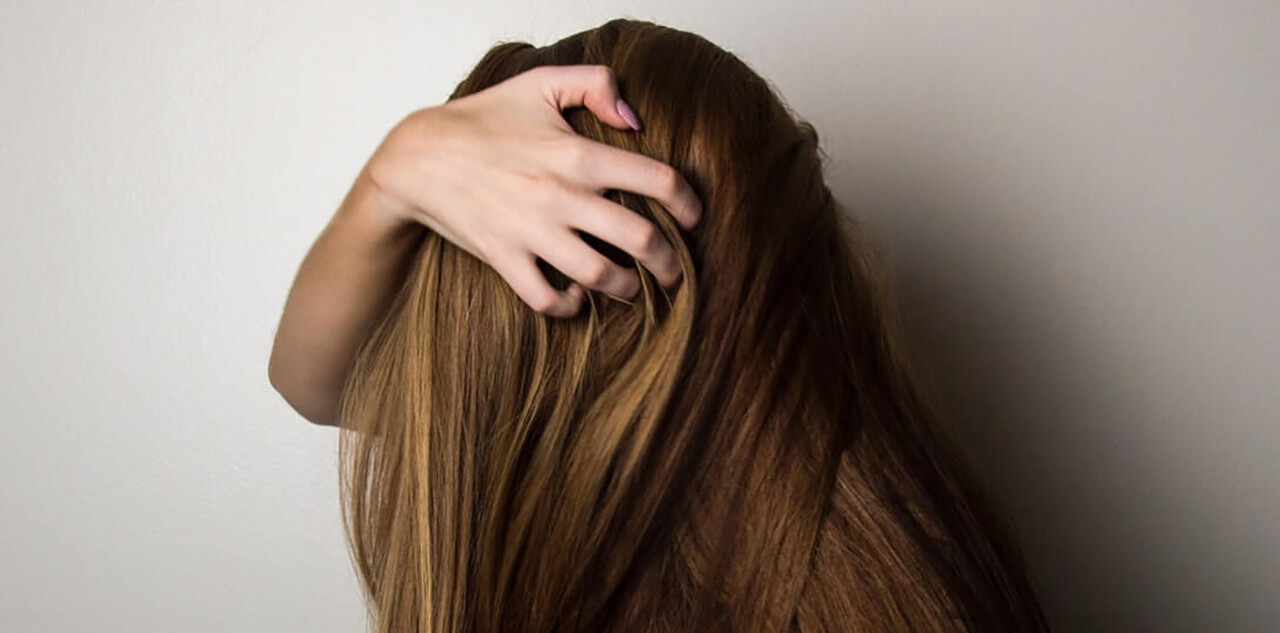 woman covering face with her hair