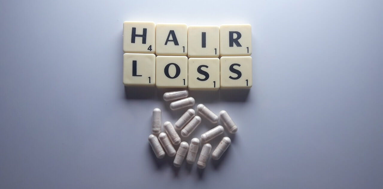 Hair loss text with white pills, hair fall and regrowth, Organic Biotin Supplements